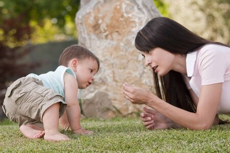 Mother playing with her little boy outdoors photo