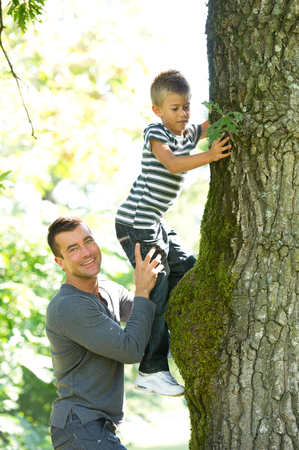 A young father helping his little boy climbing a tree photo