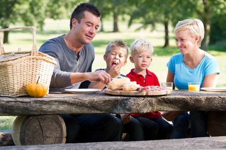 salami: Familia feliz que tiene comida campestre en un parque