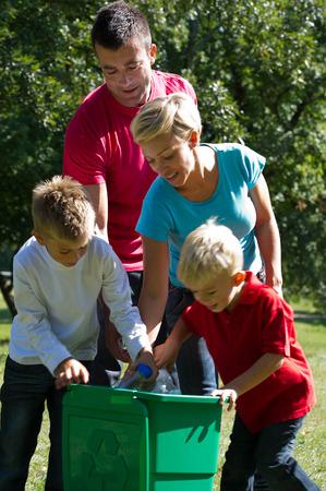 niños reciclando: Ir verde: botellas de plástico reciclado de la familia al aire libre hapy