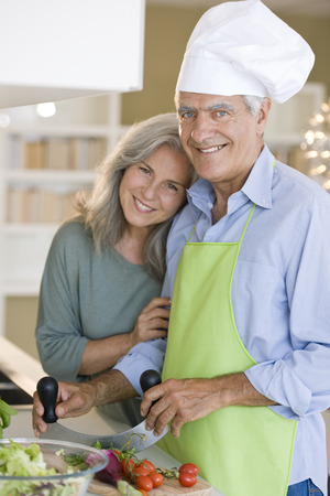 Happy senior couple cooking healthy food photo
