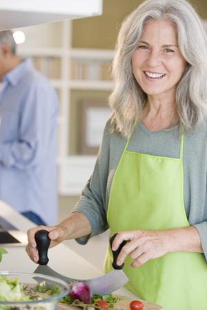 Happy senior woman cooking healthy food photo