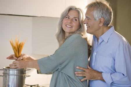 Happy senior couple cooking pasta photo