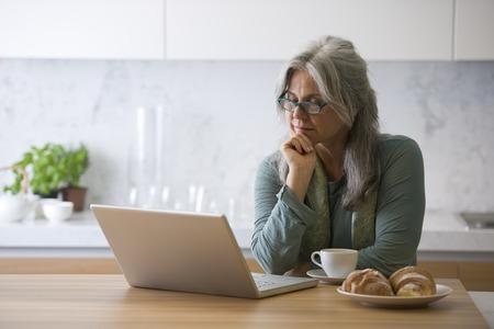 1 senior: Mujer mayor que trabaja en la PC mientras toma el desayuno Foto de archivo