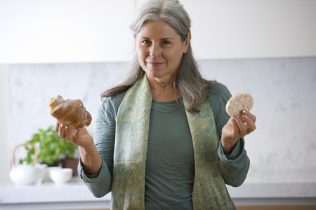 mature women only: Senior woman choosing between rice snack and brioche
