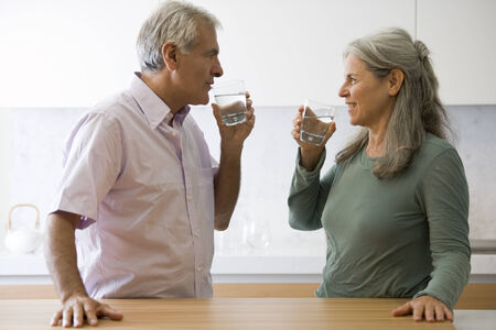 man drinking water: Senior couple drinking water in the kitchen