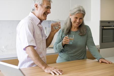 casal: Casal de idosos de água potável na cozinha