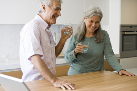 Senior paar drinkwater in de keuken Stockfoto
