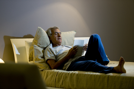 Senior man reading in the bed photo