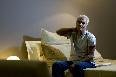Senior man wakker in het bed Stockfoto