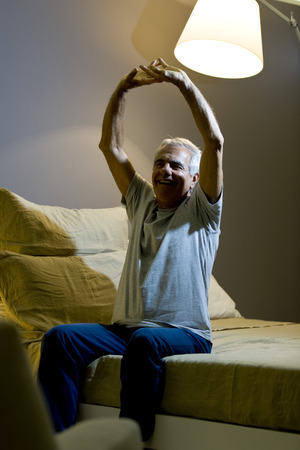 one senior man only: Senior man doing stretching on the bed