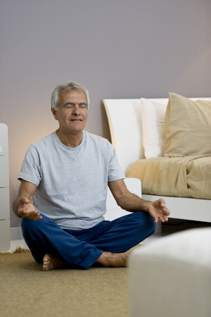 Senior man doing yogameditation in his bedroom
