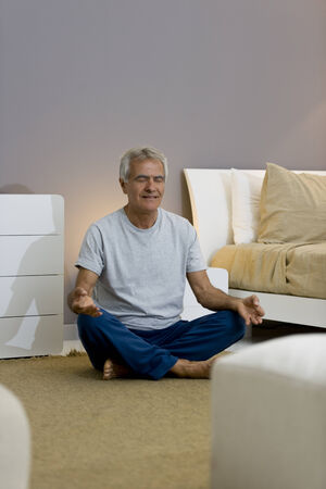 one senior man only: Senior man doing yogameditation in his bedroom