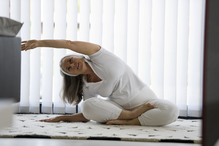 tracksuit: Senior woman doing yoga in white tracksuit