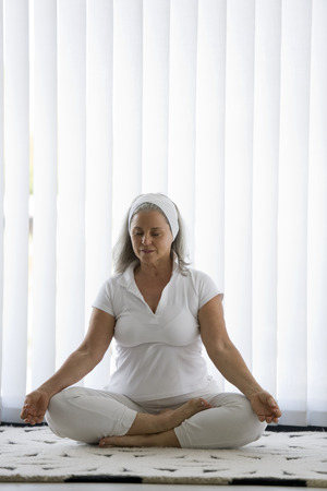 meditation room: Senior woman doing yoga in white tracksuit