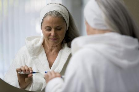 teeths: Senior woman brushing her teeths in front of the mirror