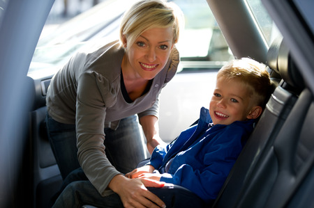 Mother fastening his sons seat belt photo