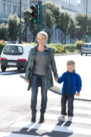 pedestrian crossing: Mother and son crossing the cross walk Stock Photo