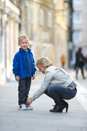 crouched: Mother helping her son to tie his shoes