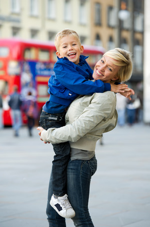 Mother embracing her son, urban scene in the background photo