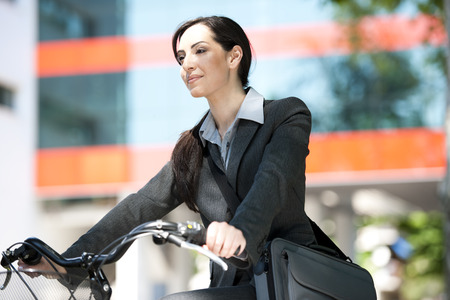 Beautiful businessw woman biking photo