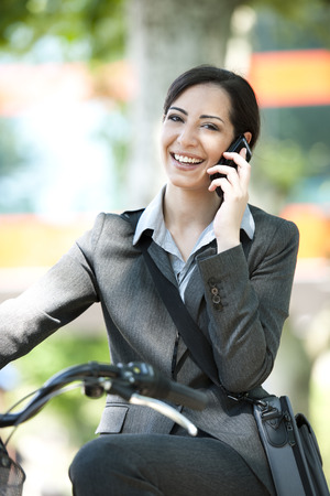 25 to 30: Businesswoman biking  and speaking on the phone