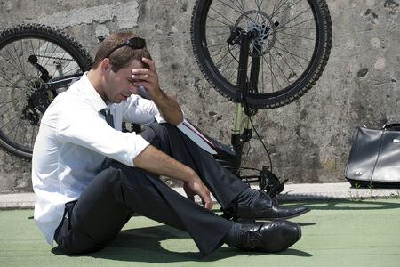 elegant business man: Businessman having troubles with his bike Stock Photo