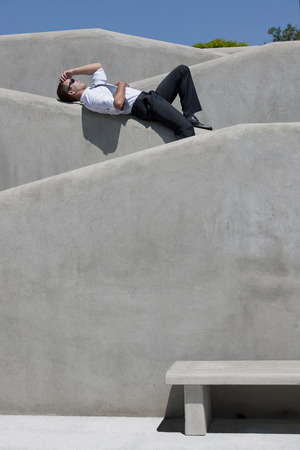 lying on side: Businessman relaxing outdoors
