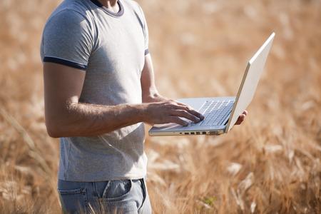 oudoors: Agronomist analysing wheat market using laptop