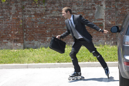 Businessman parking his car and rollerblading to work photo