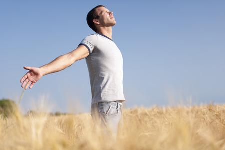Jonge man genieten van het leven, zijn armen open Stockfoto