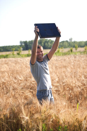 oudoors: Young man holding a solar panel model and looking at camera