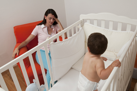 baby bed: Baby does not want to sleep, tired mother on the chair Stock Photo