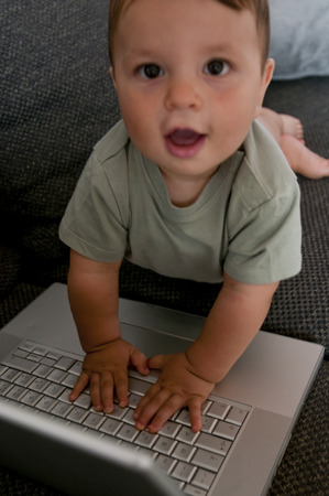 Excited baby using computer photo