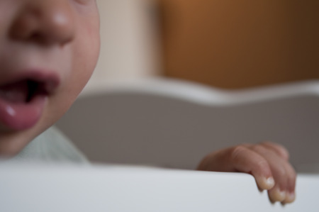 baby bed: Close-up of a little Baby bitting on crib