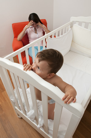 Baby does not want to sleep, tired mother on the chair photo