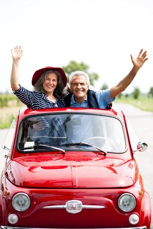 vertical image: Happy senior couple driving vintage car