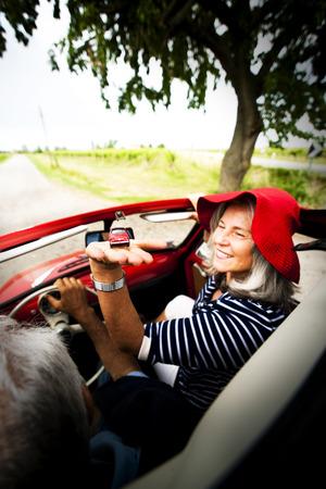 vertical image: Senior couple driving vintage car