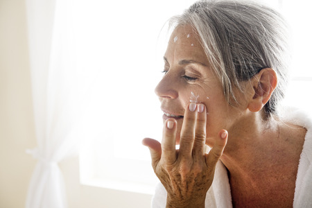 one senior woman only: Senior woman applying moisturizer on her face Stock Photo