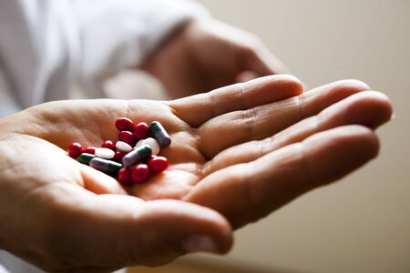 pills in hand: Human hand holding different pills Stock Photo