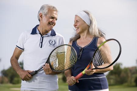 70s tennis: Happy senior couple playing tennis Stock Photo
