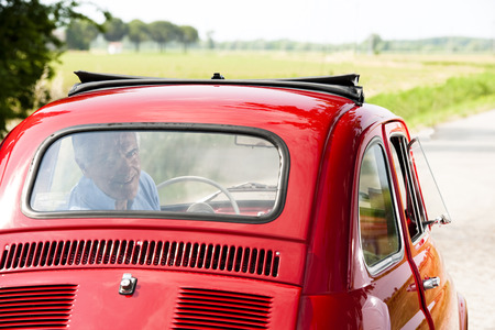 arriving: Happy senior man in a vintage car Stock Photo