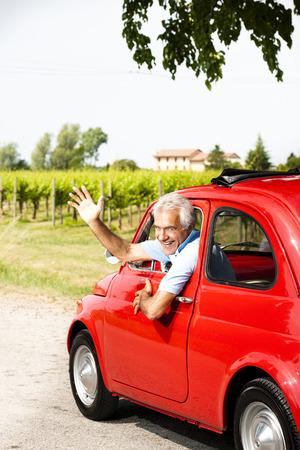 one senior man only: Senior man driving a vintage car