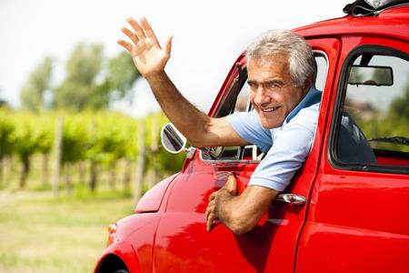 goodbye: Senior man driving a vintage car and waving