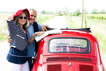 Senior couple with vintage car lookinga t a map photo