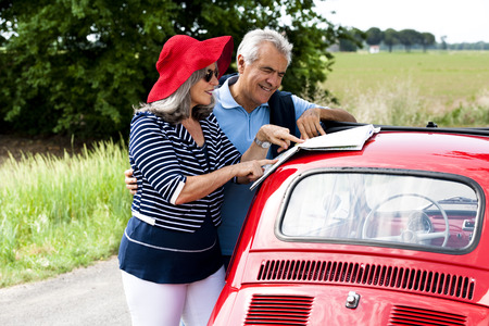 Senior couple watching a map with vintage car photo