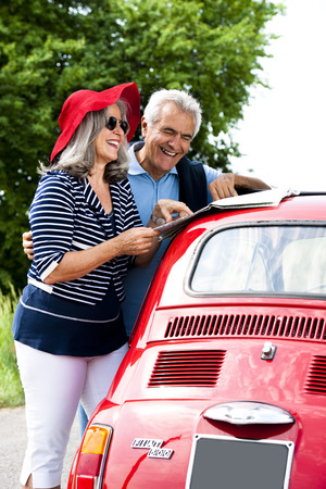 vertical image: Senior couple with vintage car lookinga t a map