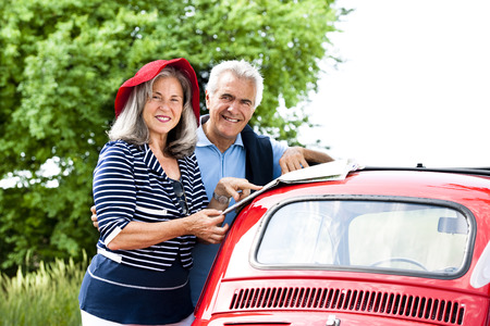 recreational area: Senior couple with vintage car lookinga t a map
