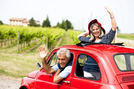 Feliz pareja mayor que conduce el coche de época