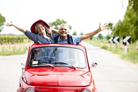 couple heureux: Couple de personnes �g�es heureux de conduire voiture de collection Banque d'images